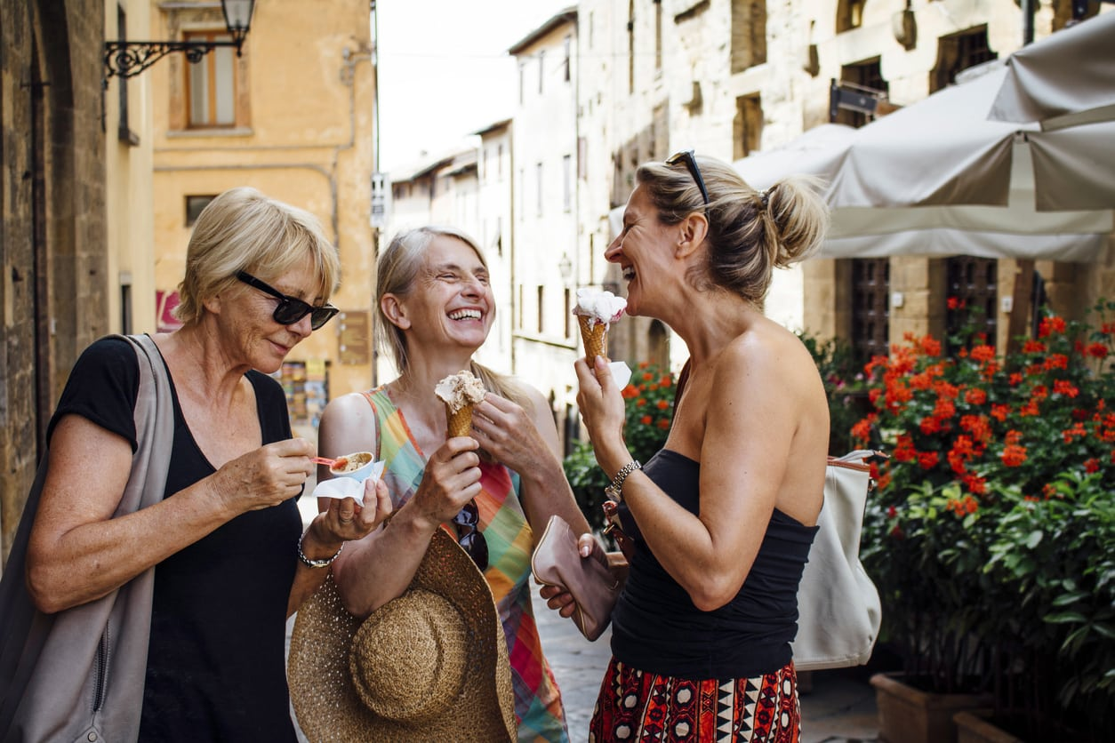 Three mature female friends standing eating Italian ice-creams while in a street in Tuscany during summer. They are smiling and facing each other and enjoying their holiday.